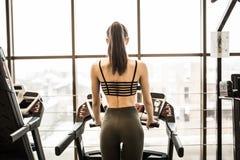 Horisontalskott av kvinnan som joggar på trampkvarnen på den vård- klubban Kvinnlig som utarbetar på en idrottshallspring på en t Arkivfoto