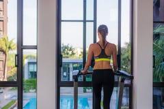 Horisontalskott av kvinnan som joggar på trampkvarnen på den vård- sportklubban på den lyxiga semesterorten Kvinnlig som utarbeta Arkivfoto