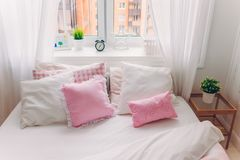Horisontalskott av säng med vit sängkläder, mjuka kuddar, fönstret med den gröna växten, ringklockan och bilden, inga personer co royaltyfri foto