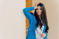 Horisontalskottet av att le den unga kvinnan för brunetten håller en hand på huvudet, iklädda formella kläder, har det toothy lee arkivfoto