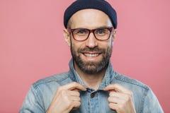 Horisontalskottet av den angenäma seende le skäggiga mannen bär exponeringsglas, och grov bomullstvillomslaget, annonserar ny tre royaltyfri fotografi