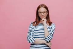 Horisontalskottet av den attraktiva kvinnliga entreprenören rymmer hakan, har säkert uttryck, bär anblickar och randig kläder, royaltyfri fotografi