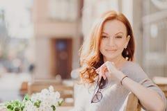 Horisontalskottet av den attraktiva nöjda röda haired kvinnan sitter på bänk, tycker om solig dag, rymmer solglasögon, andas ny l arkivfoto