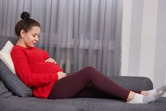 Horisontalskottet av den excpectant kvinnan håller händer på buken, tycker om komfort hemma, bär den tillfälliga röda tröjan, och arkivfoton