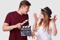 Horisontalskottet av den gladlynta kvinnan och mannen ser positivt på de, gest aktivt, har tveksamma uttryck, håll arkivbilder