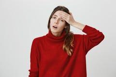 Horisontalskottet av den stressade kvinnliga kontorsarbetaren i röd tröja har huvudvärk efter hård arbetsdags, kommer hem Royaltyfria Foton