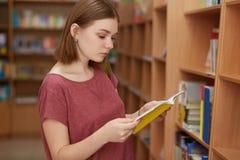 Horisontalskottet av den uppmärksamma kvinnliga avläsaren med den korta frisyren, ställningar nära shelfs med böcker i arkiv, läs royaltyfri fotografi