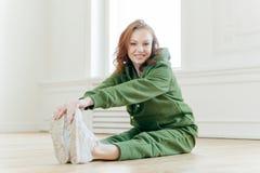 Horisontalskottet av positiva Caucasian kvinnliga elasticiteter lägger benen på ryggen muskler, gör uppvärmningsövningar, har den royaltyfri fotografi
