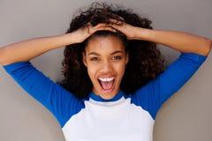 Horisontalstående av den lyckliga unga svarta kvinnan med handen i hår royaltyfria bilder