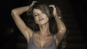 Horisontalstående av en kvinna applicera glanskanten gör upp professionelln Stranda av hår vänder mot in Royaltyfria Bilder