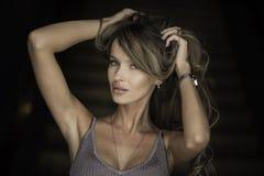 Horisontalstående av en kvinna applicera glanskanten gör upp professionelln Stranda av hår vänder mot in Royaltyfria Foton