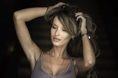 Horisontalstående av en kvinna applicera glanskanten gör upp professionelln Stranda av hår vänder mot in Arkivbild