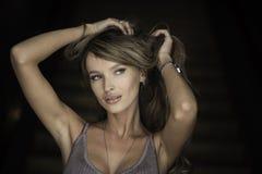Horisontalståenden av en kvinna i en svart snör åt klänningen applicera glanskanten gör upp professionelln Stranda av hår vänder  Arkivbild