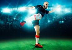 Horisontalståenden av fotbollspelaren skjuter bollen i leken Arkivbild