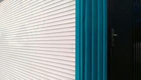 Horisontalvit och blåa vertikala band av metallrullgardiner royaltyfri bild