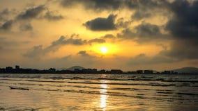 Horisonten av staden a på solnedgången och havet Arkivfoton