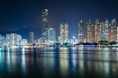 Horisonten av Tsuen som är glåmig på natten som ses från Tsing Yi, Hong Kong Royaltyfri Bild