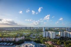 Horisontsikt med högväxta byggnader, gräs, vatten och palmträd Arkivfoto