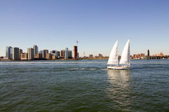Horizon de New York avec le bateau à voile sur l'eau Photo stock