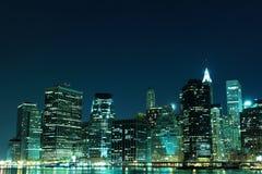 Horizon de New York City aux lumières de nuit Photographie stock libre de droits