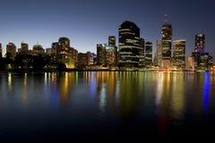 Horizon de ville au crépuscule par le fleuve Photographie stock libre de droits