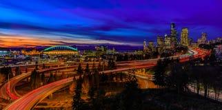 Horizon en wolkenkrabbers de de van de binnenstad van Seattle voorbij I-5 I-90 snelweguitwisseling na zonsondergang bij blauw uur stock foto
