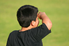 Horizon Lookout. Beautiful contrast of a Young kid in a black t-shrit looking to the horizon over a yellow green background Royalty Free Stock Photos