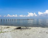Into the Horizon. Pilings stretch into a flat sea Stock Images