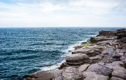 Horizon and rocky coastline with waves splashing under cloudy sk Royalty Free Stock Photos