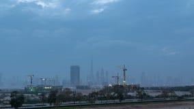Horizon van de toren van bouwkranen met wolkenkrabbers op achtergrond in de Midden-Oostendag aan nacht timelapse, Doubai stock videobeelden