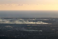 Horizon view coastline with smoke from fire stock photos