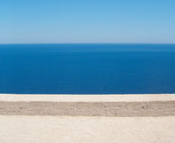 Horizons on top of horizons. Overlooking the sea from above. Looking towards the horizon, over a calm sea, from atop a castle wall. It gives an effect of stock photos