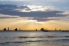 Horizont mit Segeln und Katamaranschattenbild über dem Meer bei Sonnenuntergang Lizenzfreie Stockbilder
