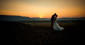 Horizontaal die huwelijk van het charmante jonggehuwdepaar wordt geschoten die bij de rand van de bergen tijdens de zonsondergang royalty-vrije stock fotografie