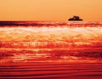 Horizontaal levendig oranje schipsilhouet in oceaan Stock Foto's