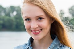 Horizontaal portret van een mooie jonge glimlachende blondevrouw in aard stock foto