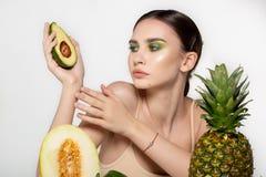 Horizontaal portret van Europese die vrouw met de helft van avocado ter beschikking, meloen en ananas in voorzijde, tegen grijs w stock foto's