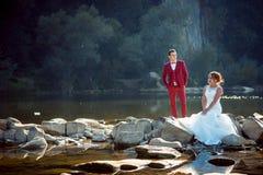 Horizontaal portret van gelukkig jonggehuwdepaar dichtbij de rivier De charmante rode hoofdbruid zit op de steen en Stock Fotografie