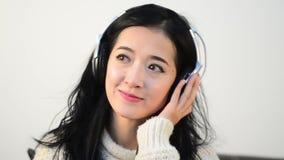 Horizontaal schot van de Aziatische muziek van de de lijstliefde van de vrouwentiener met grote Hoofdtelefoon stock video