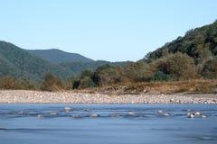 Horizontaal schot van de rivier in de vallei op de achtergrond van bergen en blauwe hemel royalty-vrije stock fotografie