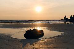 Horizontaal schot van een groot contrastsilhouet van een steen tegen de achtergrond van een Zonnige zonsondergang, het overzees e royalty-vrije stock foto