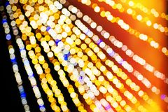 Horizontal abstract defocused bokeh illuminated garland view fro. Abstract defocused bokeh illuminated garland view from below in central city square decoration royalty free stock photo
