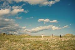 Horizontal avec des gens Trois personnes se tenant dans un domaine sur les roches avec des bras augmentés Photo stock