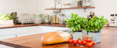 Horizontal banner with fresh ingredients on the kitchen counter top. Panoramic banner of fresh basil, tomatoes and bread on the wooden kitchen counter top royalty free stock photos