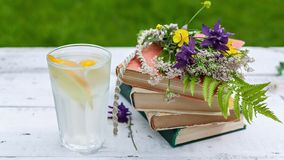 Horizontal banner: Summer vintage composition. Old books, a bouquet of wild flowers and cold lemonade on a rustic background royalty free stock images