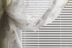 Horizontal blinds curtain. The horizontal gray shutters closed with a transparent curtain Royalty Free Stock Photo