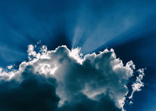 Horizontal blue dramatic cloudscape with rays of light Stock Images