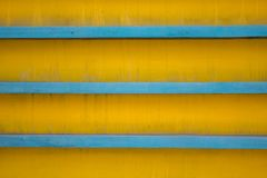 Horizontal blue lines on a dirty yellow background with shadows. rough surface texture stock photos