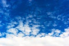 Horizontal bottom aligned white cloudscape on blue sky backgroun Stock Photos