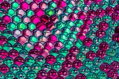 A horizontal bright colored texture of rainbow transparent hydrogel balls in green and purple color with reflection of stock photography